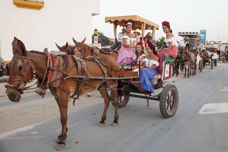 El Rocio, Spain - June 1, 2017: Pilgrims in a horse-drawn carriage on the road to El Rocio during the Romeria 2017. Province of Huelva, Almonte, Andalusia, Spain