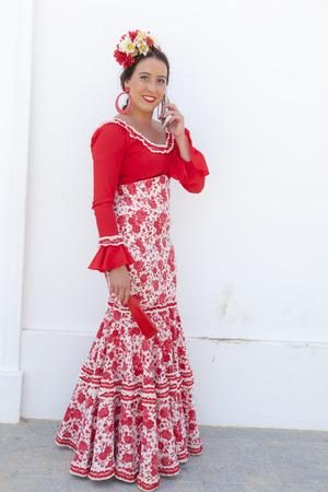 El Rocio, Spain - June 2, 2017: Female pilgrim in a traditional flamenco dress in El Rocio during the pilgrimage Romeria 2017. Province of Huelva, Andalusia, Spain