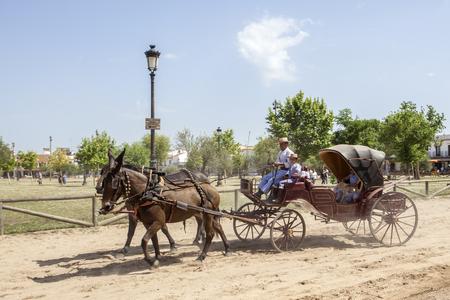 El Rocio, Spain - June 2, 2017: Pilgrims in a classic horse-drawn carriage in El Rocio during the pilgrimage Romeria 2017. Province of Huelva, Andalusia, Spain