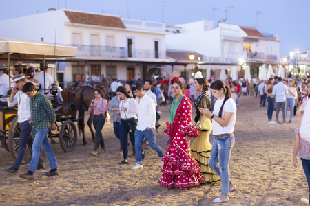 El Rocio, Spain - June 2, 2017: Pilgrims in traditional flamenco dresses in El Rocio during the pilgrimage Romeria 2017. Province of Huelva, Andalusia, Spain