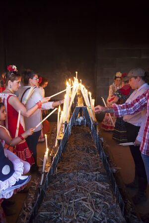 El Rocio, Spain - June 2, 2017: Pilgrims in traditional spanish dress light up candles in the hermitage of El Rocio during the Romeria 2017. Andalusia, Spain