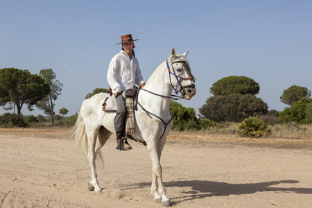 El Rocio, Spain - June 1, 2017: Pilgrims on horseback in  traditional spanish dress on the road to El Rocio during the Romeria 2017. Province of Huelva, Almonte, Andalusia, Spain