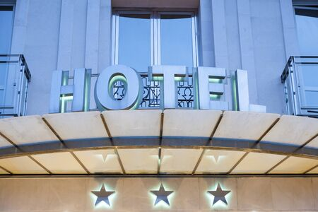 Three stars hotel facade illuminated at night Stock Photo