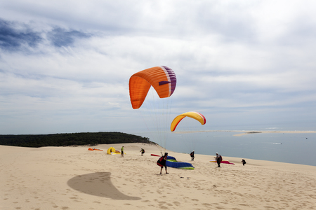 Paraglider at  the Dune of Pilat - the tallest sand dune in Europe. The dune is located in La Teste-de-Buch in the Arcachon Bay area, France