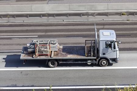 Flatbed truck loaded with scaffolds driving on the highway Stock Photo