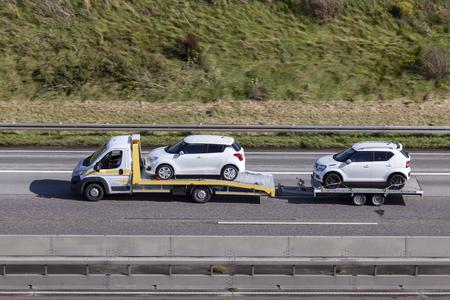 프랑크푸르트, 독일 -2011 년 9 월 19 일 : 고속도로에서 새로운 스즈키 자동차와 함께로드 된 트레일러와 피아트 두 카토 자동차 운송업자 에디토리얼