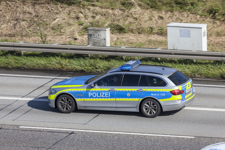 squad: Frankfurt, Germany - Sep 19, 2017: BMW five series police car driving on the highway in Germany