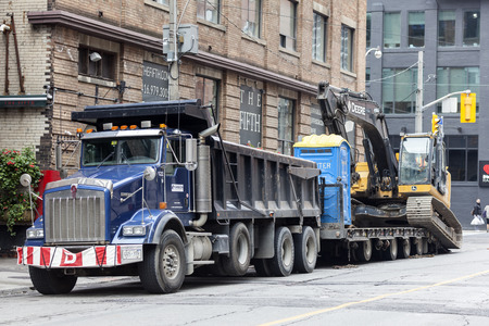 Toronto, Canada - Oct 14, 2017: Kenworth T880 dump truck with an excavator on a trailer in a street downtown of Toronto