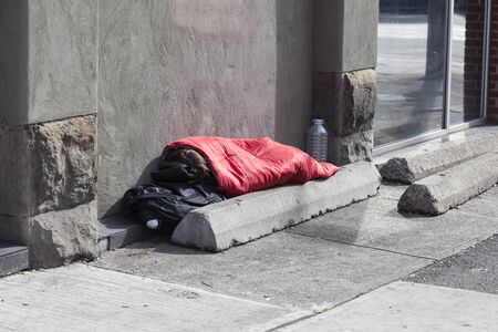 Homeless person sleeps on the sidewalk in the city