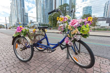 Classic tricycle or trike with flowers in the city