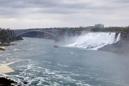 The American Falls waterfalls and the Rainbow bridge at the Niagara River. New York, United States