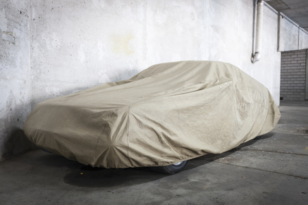 Car under a protective cover parked in parking garage Banco de Imagens - 91260332