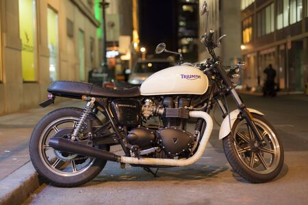 Toronto, Canada - Oct 21, 2017: Classic Triumph Bonneville motorcycle parked in a city street at night