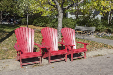 Three empty red chairs in an urban park in Toronto, Canada Banco de Imagens - 91422241