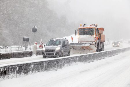 Snow plow truck on the highway during a blizzard in winter Banco de Imagens - 91941212