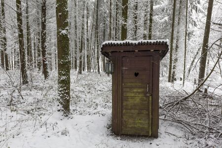 Wooden outdoor toilet in a snowy winter forest Banco de Imagens - 92091834