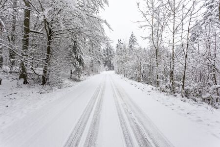 Snow covered road in a snowy white winter forest in Hesse, Germany Banco de Imagens - 92262388