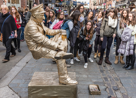 LONDON, UK - April 11, 2014 : Living statue street performer amazing crowds in Covent Garden London by appearing to balance unsupported whilst drinking a beer.