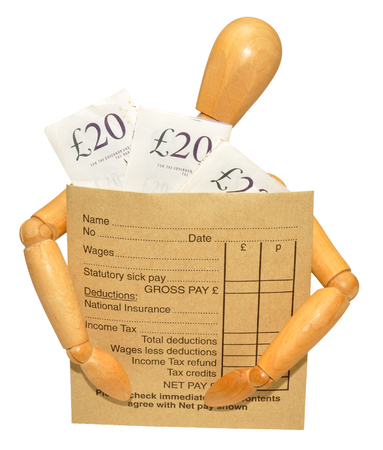 A wooden mannequin with arms around a wage packet envelope with banknotes, isolated on a white background photo