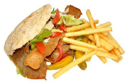A takeaway doner kebab in a pita bread with fries, isolated photo