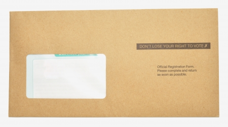 official ballot: A voter registration form in a brown envelope with don't loose your right to vote printed on it, isolated on a white background  Stock Photo