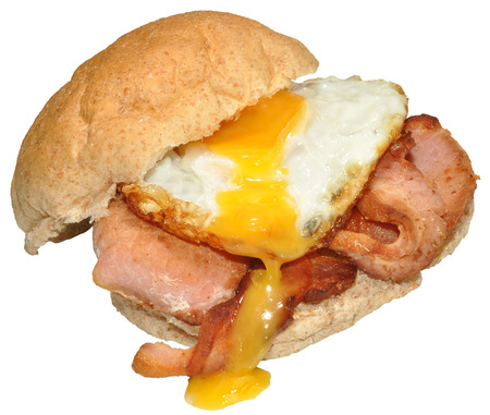 Fried egg and bacon on a wholemeal bread roll, isolated on a white background