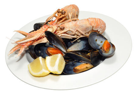 A bowl of cooked langoustine and mussels, isolated on a white background  photo