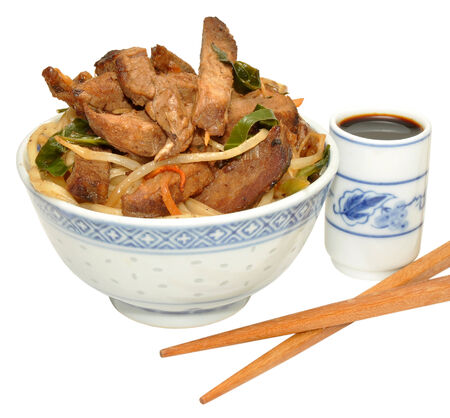 Beef stir fry meal in a traditional Chinese decorated bowl, isolated on a white   photo