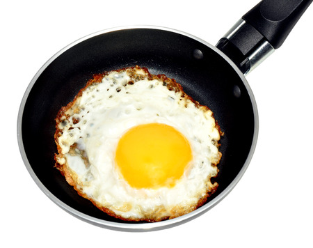 Single fried egg in a non stick frying pan, isolated on a white background  photo