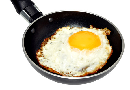 non stick: Single fried egg in a non stick frying pan, isolated on a white background