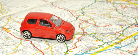 A small red toy car on a paper road map