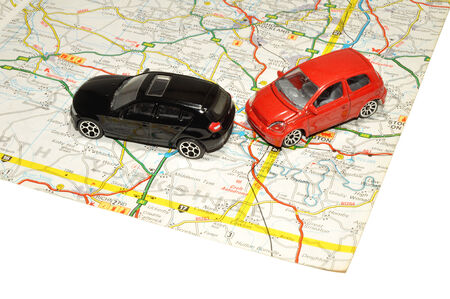 Two small red and black toy cars on a paper road map