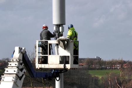 Two workmen on a hydraulic boom lift repairing a telecommunications mast  photo