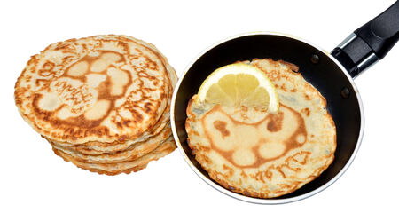 Freshly made pancakes with lemon and frying pan, traditionally eaten in England on Shrove Tuesday also known as pancake day, isolated on a white background  photo