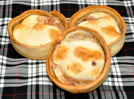 Three traditional Scottish meat filled pies with black and white tartan background photo