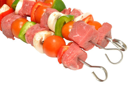 Raw uncooked beef kebabs with vegetables, isolated on a white background  photo