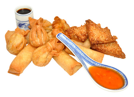 Chinese appetizer snacks with spring rolls, wontons and prawn sesame seed toast with sweet chilli dip, isolated on a white background  photo