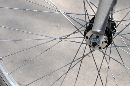 peddle: Front wheel and forks of  a bicycle with wire spokes Stock Photo