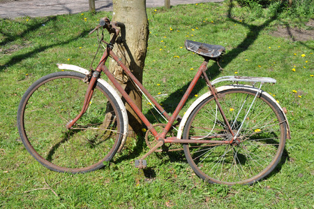 out dated: A dirty old rusty peddle bike leaning against a tree in sunshine  Stock Photo