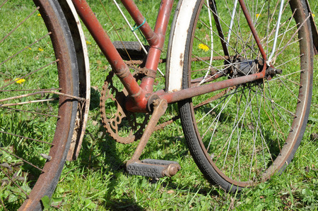 out dated: A dirty old rusty peddle bike on green grass in sunshine