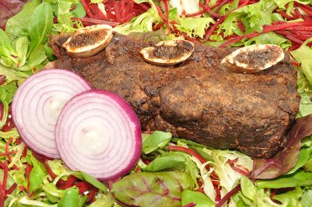 고기의: 양파 슬라이스와 샐러드 잎 배경으로 고기 로스트 비프 리브 스톡 사진