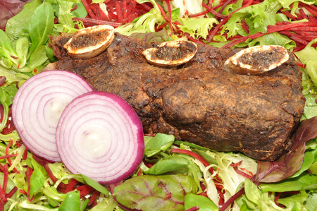 meaty: Meaty roast beef rib with onion slices and salad leaf background