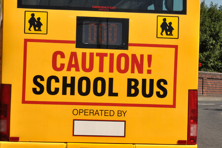 Rear of a yellow school bus with caution sign and children crossing symbols  photo