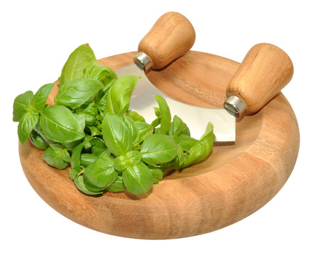 Fresh basil herb leaves on a circular wooden herb chopping board with a mezzaluna chopping knife, isolated on a white background  photo