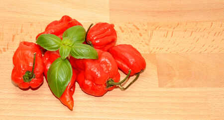 Hot red scotch bonnet peppers on a wooden background  photo