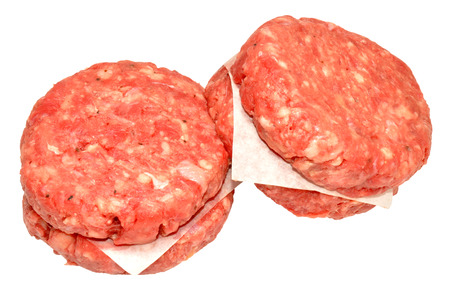 Four raw quarter pound beef burgers, isolated on a white background  photo
