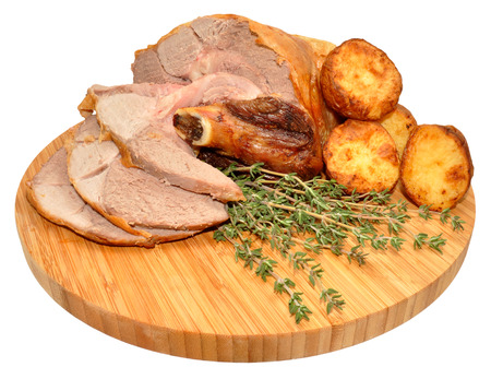 sheep skin: Partially carved roast leg of lamb with fresh thyme herb and roasted potatoes on a wooden chopping board, isolated on a white background. Stock Photo