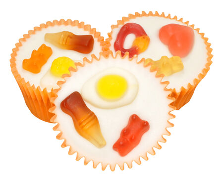 chewy: Iced cupcakes decorated with chewy candy shapes, isolated on a white background.