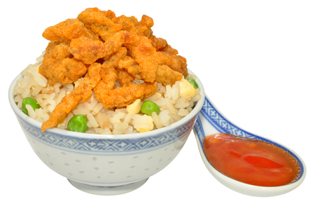 Chinese crispy beef and rice in a decorated bowl with chilli sauce, isolated on a white background. photo