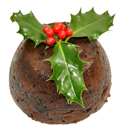 Traditional Christmas pudding with holly leaves and red berries, isolated on a white background.